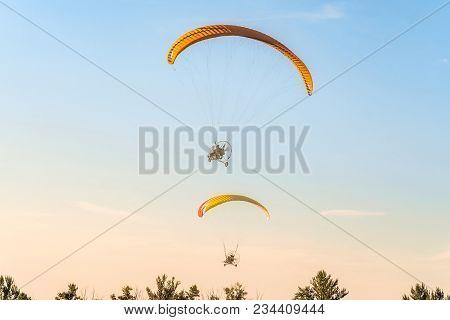 Flight of two motor paragliders trike skyward. Flight on motor gliders in the blue sky over the green trees. stock photo
