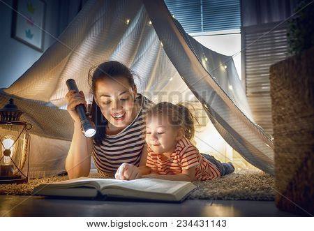 Family bedtime. Mom and child daughter are reading a book in tent. Pretty young mother and lovely gi