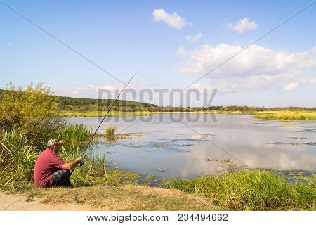 Fisherman on the shore of the lake. Fishing adventure against the backdrop of the scenic landscape of Lake Khanka in the far east of Russia stock photo