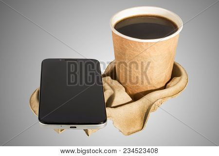smartphone and Cup of coffee in a cardboard stand on the grey background. the concept of business Breakfast stock photo