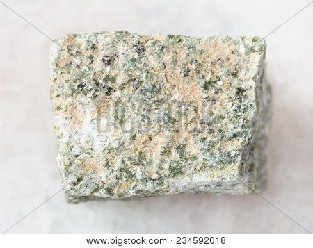 macro shooting of natural mineral rock specimen - rough quartz-mica schist stone on white marble background stock photo