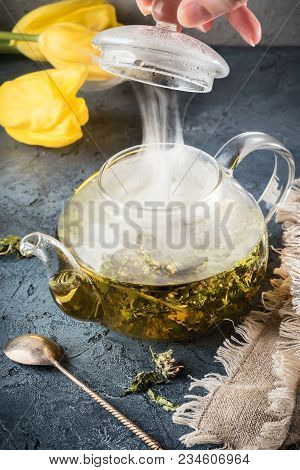 Hand open lid of kettle with herbal tea from peppermint boiled hot water drops condensate will rise steam teapot with detox beverage on gray stone background Concept food health tea ceremony for healthy medicine treatment. stock photo
