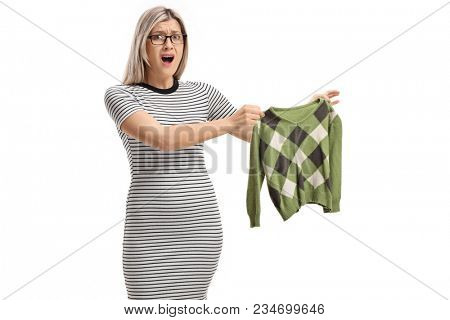 Shocked young woman holding a shrunken blouse and looking at the camera isolated on white background stock photo