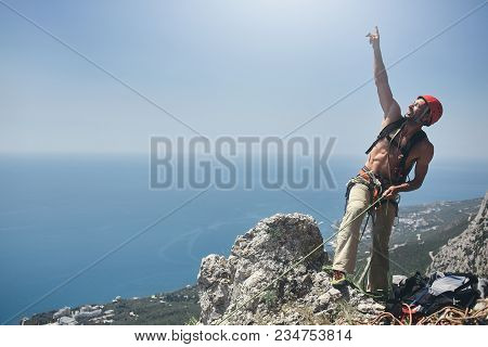 man rock climber stands on the top of the cliff and belays a partner and shows up to the sky by the hand stock photo