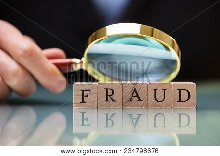 Close-up Of A Businessperson's Hand Holding Magnifying Glass Over Fraud Blocks stock photo