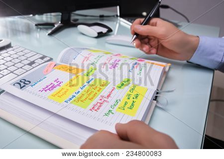 Businessman's Hand Writing Schedule In Diary With Pen At Workplace stock photo