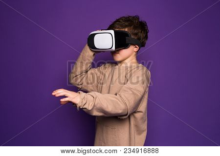 Spend time with pleasure! Young boy wearing VR-headset glasses of virtual reality having a great time spending indoors. stock photo