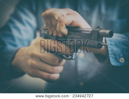Male hands reloading gun. Close up view. stock photo
