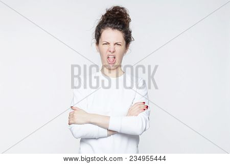 Funny Caucasian woman closes eyes and opens mouth with tongue, sees something sour, isolated over white background. Unhappy beautiful young female wears casual shirt, makes grimace or pulls face. stock photo