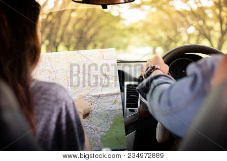 Asian man and woman using map on road trip and Happy young couple with a map in the car. Blurred and Soft focus stock photo