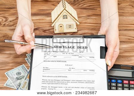 Female's hands holding clipboard with mortgage deed and pen over table with money, calculator and model of house. stock photo