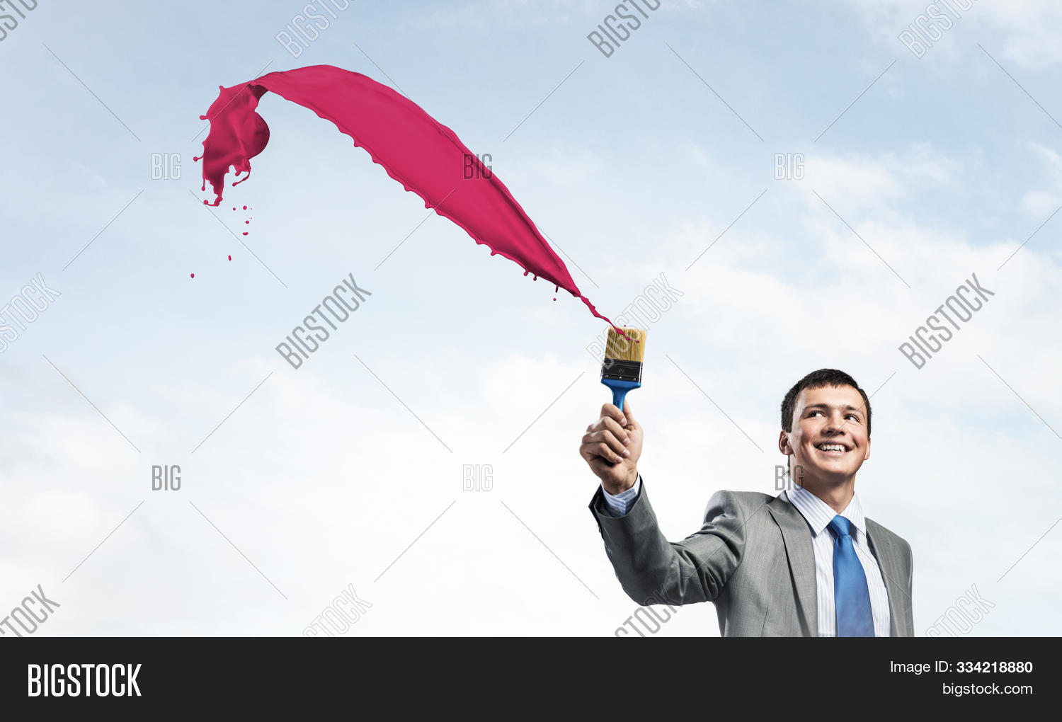 Smiling creative businessman painter holding paintbrush. Portrait of joyful handsome man in business suit and tie. Pink paint splash on blue sky background. Ambitions and creativity in business