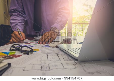 Business man in office and calculate financial plan sales. Working on desktop computer making business plan, business investment advisor consulting on the financial report, plan a marketing plan at business office. Business accounting plan concept. stock photo