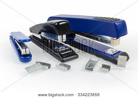 Paper manual hand-held staplers different sizes and expendable metal staples to them on a light surface stock photo