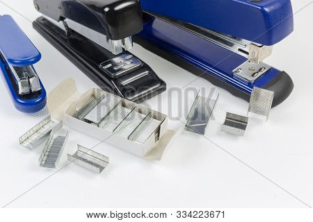 Expendable metal staples to the paper staplers in small box and beside against several different staplers on a light surface close-up in selective focus stock photo