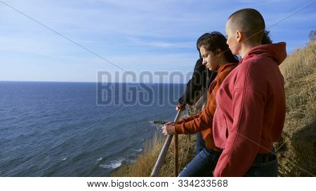 Family vacation, lifestyle concept. Happy bald mother, children on a hill with picturesque views of high cliffs and the sea. stock photo