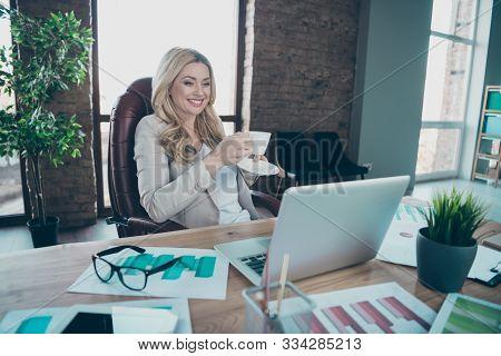 Photo of beautiful blond business lady looking notebook table holding coffee beverage speaking skype partners break sitting chair formalwear blazer in modern office stock photo