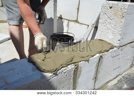 Bricklayer builder laying autoclaved aerated concrete blocks, aac.  Autoclaved aerated concrete blocks walling installation with concrete glue stock photo