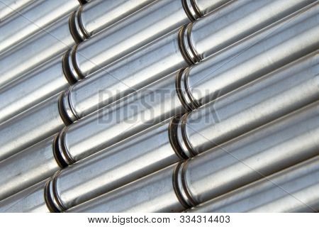 Metal parts with shiny steel cylindrical surface closeup. Angled view of the disassembled lithium ion form factor cell 2170 battery pack. Abstract Industrial background with selective focus. stock photo