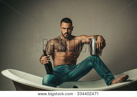 Handsome bearded shirtless man in jeans with sexy body in bathroom. Sexual macho man in bath. Strong muscular tattoed man holding champagne bottle and posing in bathroom stock photo