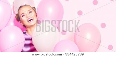 Beauty girl with colorful air balloons laughing over pink background. Beautiful Happy Young woman on birthday holiday party. Joyful model having fun, playing and celebrating with pastel color balloon  stock photo