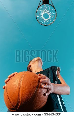 Sports and basketball. A young teenager in a black tracksuit stands with a ball in his hands and prepares to throw the ball into the ring. Blue sky with hoop. Bottom view. Copy space stock photo