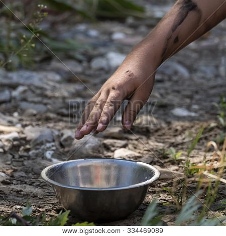 A dirty childrens hand reaches for a metal plate standing on the ground. Close-up. The concept of slavery, hunger, violence and child trafficking. Violation of the law, kidnaping, illegal exploitation. stock photo