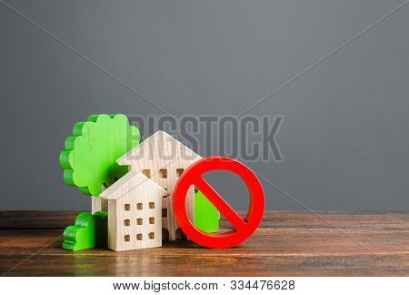 Residential buildings figurines and red prohibition symbol NO. Concept of inaccessibility, lack of housing. No opportunity buy a house or pay for rent. BThe restricted area for civilian infrastructure stock photo