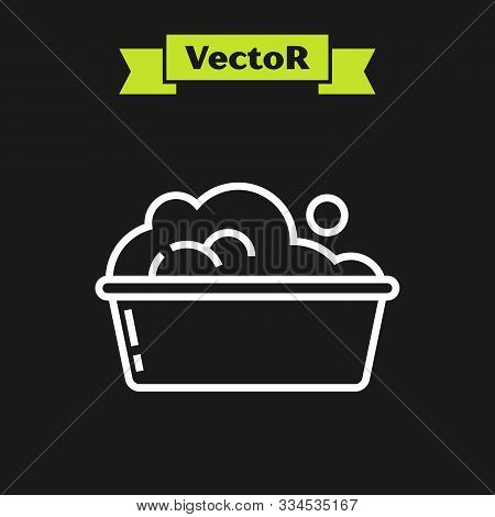 White line Plastic basin with soap suds icon isolated on black background. Bowl with water. Washing clothes, cleaning equipment. Vector Illustration stock photo