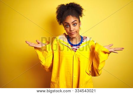 Young african american woman wearing rain coat over isolated yellow background clueless and confused expression with arms and hands raised. Doubt concept. stock photo