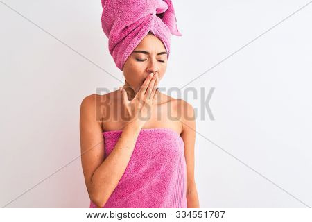 Young beautiful woman wearing shower towel after bath over isolated white background bored yawning tired covering mouth with hand. Restless and sleepiness. stock photo