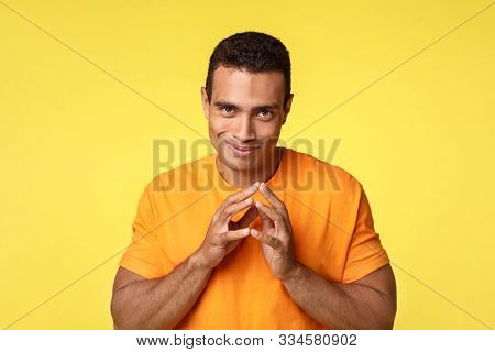 Sly sneaky young man have secret evil plan, smirk devious and steeple fingers, prepared vengence, standing yellow background joyful, want make something bad, wear orange t-shirt stock photo