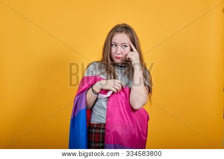Boring young caucasian woman posing isolated on orange background in studio wearing casual shirt, keeping finger on head covered bisexual flag stock photo