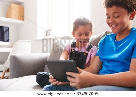 Brother And Sister Sitting In Lounge At Home Watching Movie On Digital Tablet Together stock photo