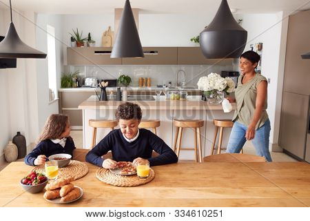 Mother In Kitchen Helping Children With Breakfast Before Going To School stock photo