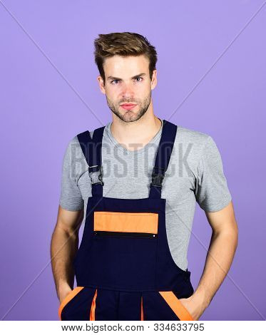 carry out repairs. man builder in work clothes. professional repairman. man build house. building and construction. worker purple background. skilled architect repair and fix. turnkey project stock photo