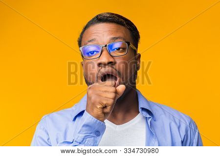 Boredom. Sleepy Afro Man Yawning Covering Mouth With Hand Standing Over Yellow Background. Studio Shot stock photo