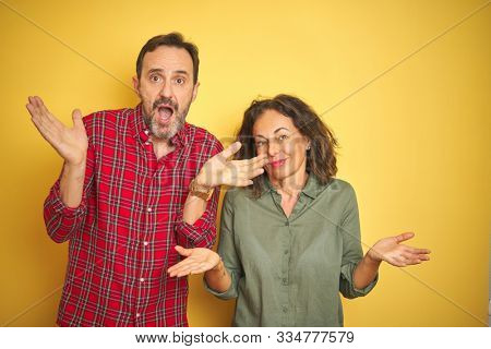 Beautiful middle age couple over isolated yellow background clueless and confused expression with arms and hands raised. Doubt concept. stock photo