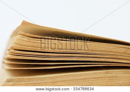 Yellowed pages of an old thick textbook. Literature and philology. Library, archives and bibliophilia. Close-up. stock photo