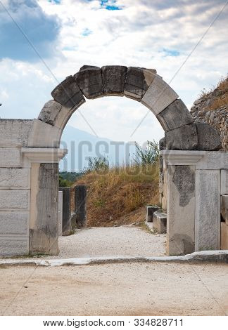 Stone archway with a carved keystone that is part of an ancient gate. Hillside and rock wall are in the background and cloudy skies above. Photographed in Philippi Greece. stock photo