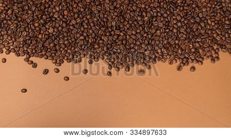 Dark brown whole coffee beans on wood background with copyspace stock photo