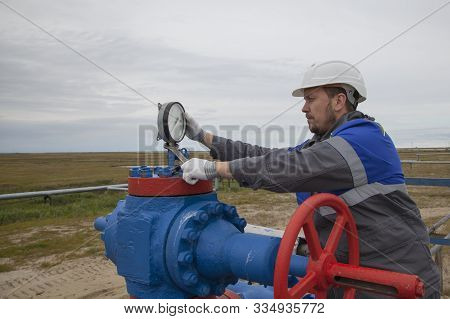 Gas operator, The operator operates the gas well with a torch.The mechanic - the repairman , Oil, gas industry. gas conditioning equipment and valve armature stock photo