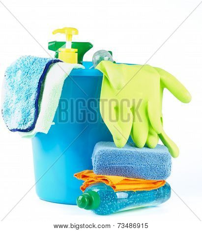 Arrangement of Cleaning Bottles and Sprays into Blue Bucket with Bath Sponge and Protective Gloves isolated on white background stock photo