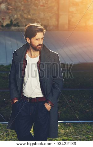 Portrait of elegant fashionable adult man dressed in coat walking on tramline in urban setting stylish hipster man walking on the street at sunny evening flare sunshine stock photo
