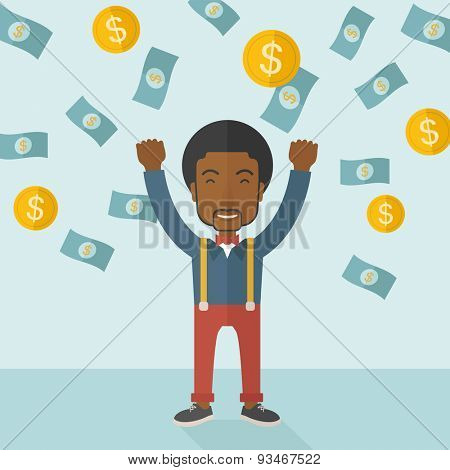 A young and cheerful african gentleman standing under falling raining money shower a coin and bill d