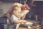 Mom with her 2 years of age kid cooking occasion pie in the kitchen to Mothers day, easygoing way of