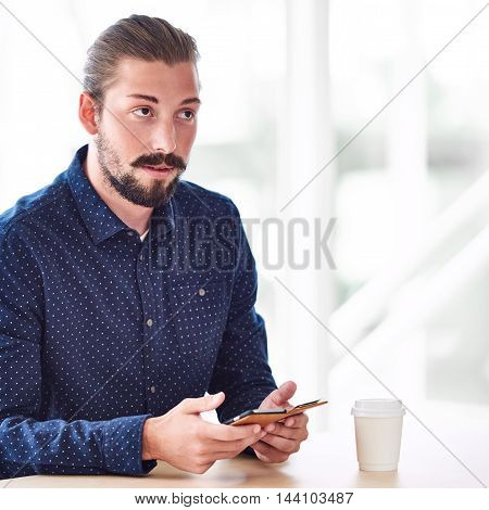 square image of trendy hipster holding a mobile phone in his hands, busy looking up but not into the camera with ato go coffee on the table in front of him. stock photo