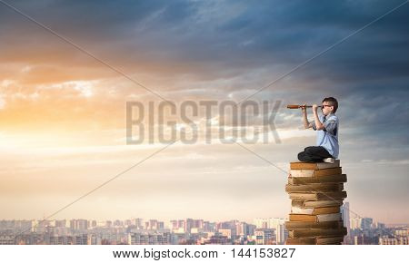 Kid of school age sitting on pile of books and looking in spyglass stock photo