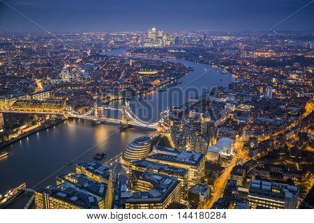 London England - Aerial Skyline view of London with the iconic Tower Bridge the Tower of London and skyscrapers of Canary Wharf at blue hour