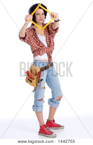 young woman with tool belt is holding a square-folded metering rule in front of her face stock photo